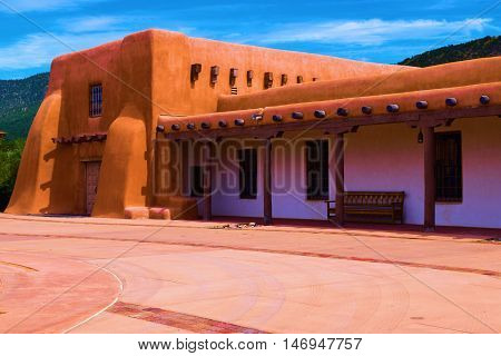 Southwestern adobe style building with mountains beyond taken in Santa Fe, NM