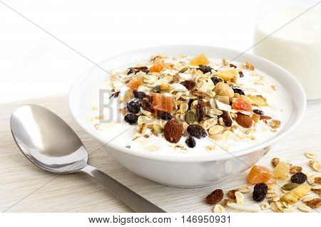 Breakfast Bowl Of Fruit And Nut Muesli With Milk And Spoon. Spilled Muesli.