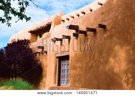 Southwestern adobe style building surrounded by lush gardens taken in Santa Fe, NM
