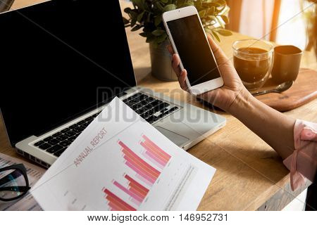Top view of young working woman using laptop and reading report graphs charts document at work. Business woman working at her desk.