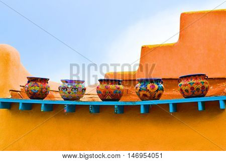 Colorful pots placed on an outdoor shelf taken on an adobe style building taken in New Mexico