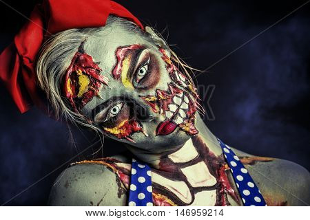 Frightening pin-up zombie girl over dark background.  Body-painting project. Halloween make-up. Horror.