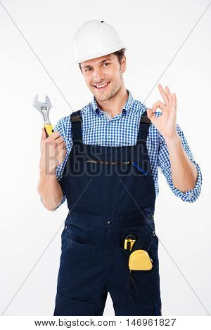 Cheerful young man builder in hard hat holding wrench and showing ok sign