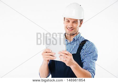 Happy smiling male builder using pc tablet isolated on a white background