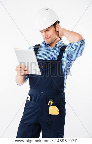Thoughtful confused builder in helmet scratching his head and holding pc tablet isolated on a white background