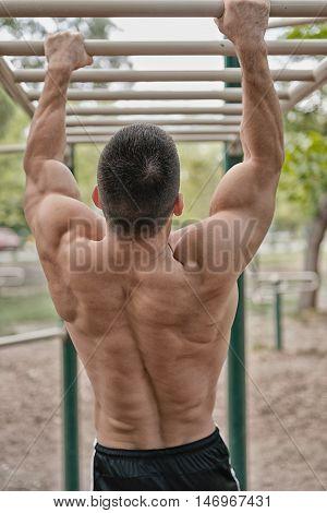 Muscular Man Exercising On Monkey Bars