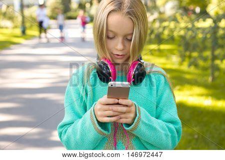 Little Beautiful Girl Enjoys The Phone. She Headphones.