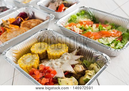 Healthy food delivery, daily ration. Take away of natural organic low carb diet of vegetables, fish and meat. Fitness nutrition in foil boxes on white wood background