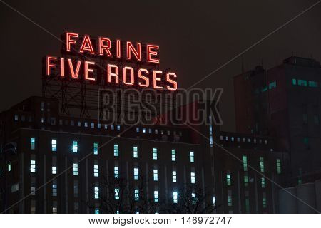 MONTREAL CANADA - January 25 2015: The landmark Farine five roses building and red neon sign at night. The flashing sign has illuminated the city since 1948