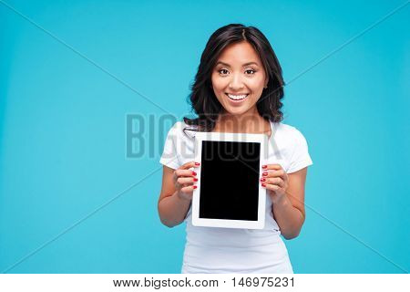 Smiling casual woman showing blank tablet computer screen isolated on a blue background