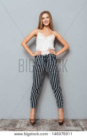 Full length portrait of a beautiful confident young girl looking at camera and holding arms on her hips isolated on the gray background