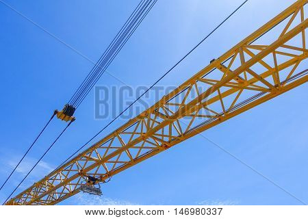Crane boom structure and metal sling on blue sky background