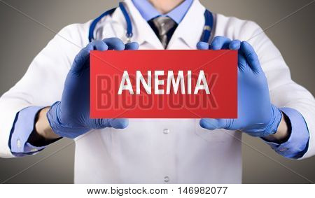 Doctor's hands in blue gloves shows the word anemia. Medical concept.