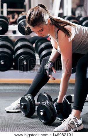 Athletic brunette pumping up muscles at gym. Close-up of strength training of young woman, female arm wrestler workout at professional gymnasium