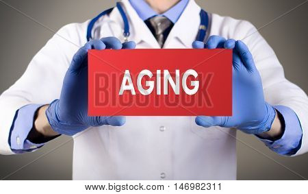 Doctor's hands in blue gloves shows the word aging. Medical concept.