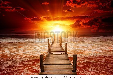 Pier for boats into the sea. Bright sunrise over the ocean.