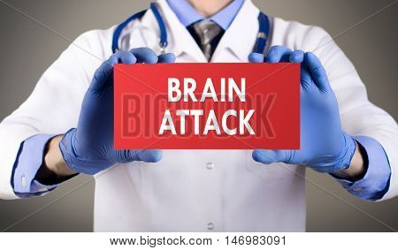 Doctor's hands in blue gloves shows the word brain attack. Medical concept.