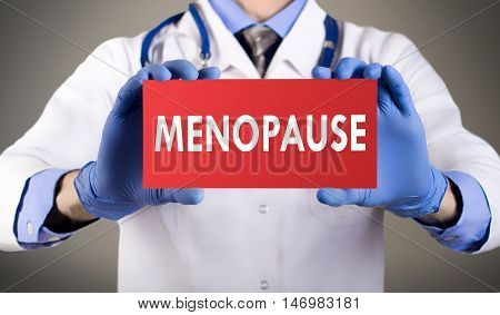 Doctor's hands in blue gloves shows the word menopause. Medical concept.