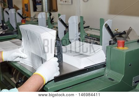 Binding of brochures in printing house. Closeup