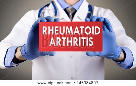 Doctor's hands in blue gloves shows the word rheumatoid arthritis. Medical concept.