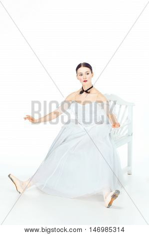 Ballerina in white dress sitting on white chair like a doll studio white background.