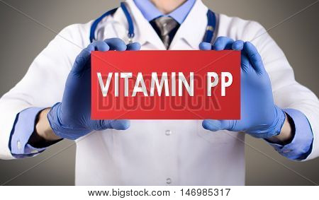 Doctor's hands in blue gloves shows the word vitamin pp. Medical concept.