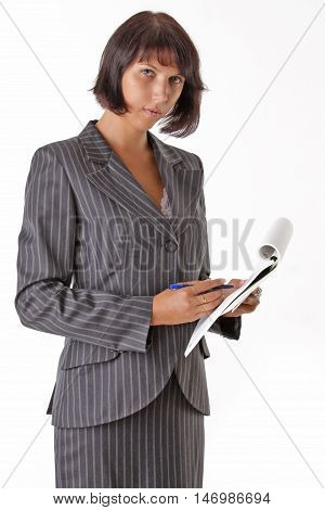 beautiful business woman wrote in a notebook and looks at camera