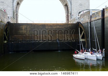 UGLICH RUSSIA - JULY 19 2016: Teams of yachts are on sluicing in navigable sluice of Uglich hydroelectric power station Russia