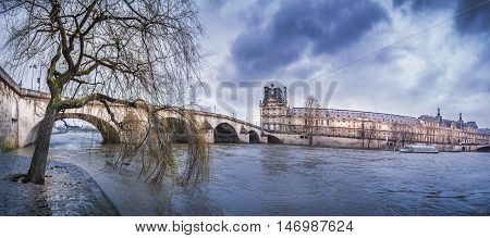 Dark clouds over Royal Bridge and Seine River - The Pont Royal Louvre Palace and the river Seine on a rainy day of February in Paris France.