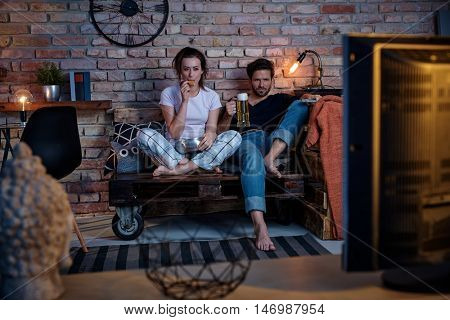 Young couple watching tv at home, drinking beer, eating biscuit.