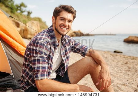 Smiling young man tourist sitting in touristic tent at the beach and looking at camera