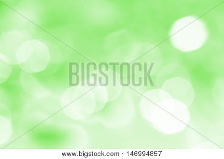 Abstract green background with white spots and patches of light