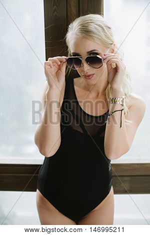 girl in sexy body posing next to a window holding her hands near the sunglasses Sunglasses in the hands of women