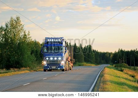SALO, FINLAND - SEPTEMBER 9, 2016: Blue Volvo FH16 Kung Fu Panda show truck for construction with bright lights on scenic rural road in evening dusktime.