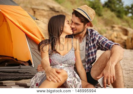 Close up of a young happy beautiful couple sitting at the tent at the beach and kissing