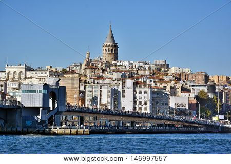 Istanbul, Turkey - November 3, 2015. Galata skyline in Istanbul, with Galata bridge, Galata tower, residential and commercial buildings and people.