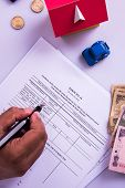 Indian man or accountant person filing Indian income tax returns form or ITR document showing indian currency, house model, toy car and calculator over white table top, selective focus poster