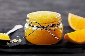 Orange body scrub with sugar and coconut oil in glass jar on black table. Homemade cosmetic for peeling and spa care. poster