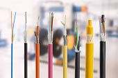 Collection of fiber optical cables on blurry production room background. Loose tubes with optical fibres and central strenght member waterblocking glass yarn and ripcord multimode or single mode poster
