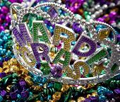 A colorful Mardi Gras crown on top of a group of colorful beads poster
