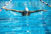 Energetic female swimmer swims in the butterfly style in the swimming pool. Woman wears a black-lime swimsuit, a white swim cap and swim glasses. Outdoors. Horizontal. poster
