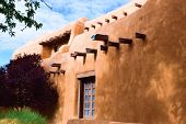 Southwestern adobe style building surrounded by lush gardens taken in Santa Fe, NM poster