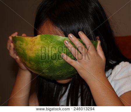 Little Asian Girl Eating Watermelon Rind Against Face