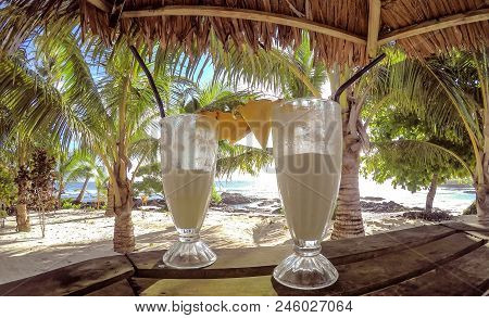 Half Full Glasses Of Tropical Pina Colada Cocktail Drink With Pineapple Garnish In Glass With Straws