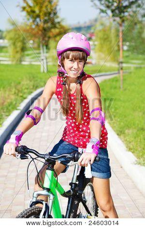 Teenage girl in protective helmet on a bike