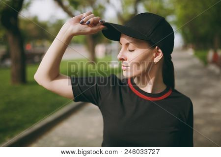 Young Athletic Beautiful Brunette Girl In Black Uniform And Cap With Closed Eyes Standing And Keepin
