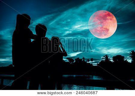 Silhouette Of Mother And Children Looking At Red Super Moon Or Blood Moon On Colorful Sky With Cloud