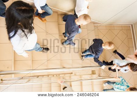 Pupils In A School Hallway Going Down The Stairs After The Lesson. Active Schoolchildren Run Away, M