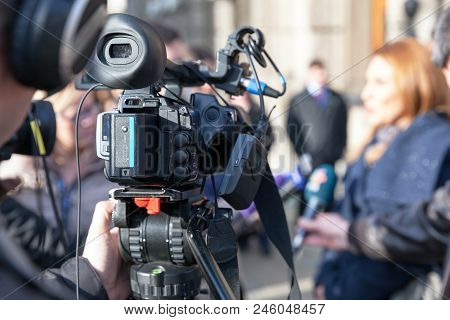 Media Interview Or A Press Conference With A Video Camera And Cameraman In Focus.