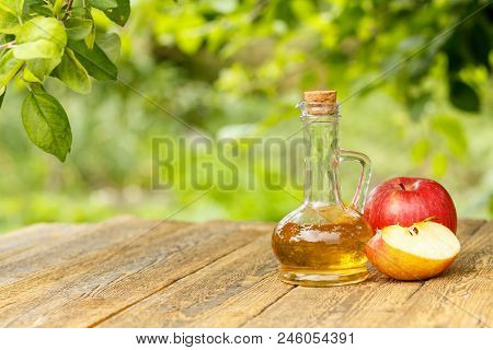 Apple Vinegar In Glass Bottle With Cork And Fresh Red Apples On Old Wooden Boards With Branch Of App
